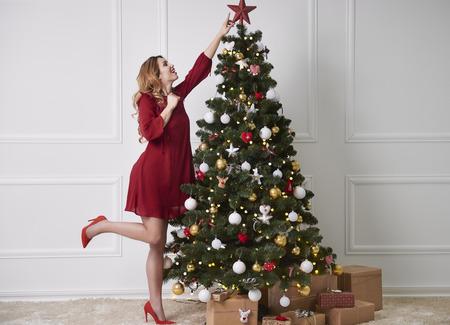 Cheerful woman decorating the christmas tree Standard-Bild - 111285425