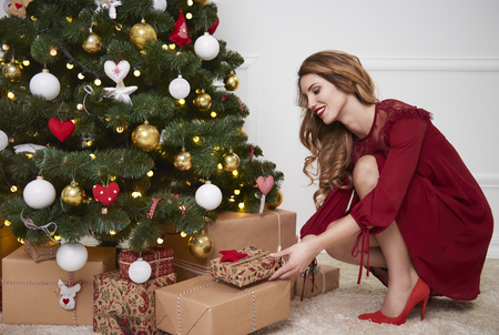 Elegant woman putting gifts under christmas tree Standard-Bild - 111285441