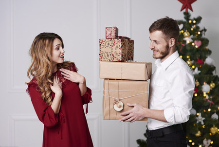 Man giving stack of gifts to woman