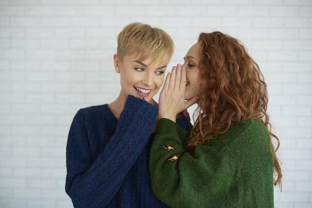 Chica susurrando un secreto a su amiga Foto de archivo