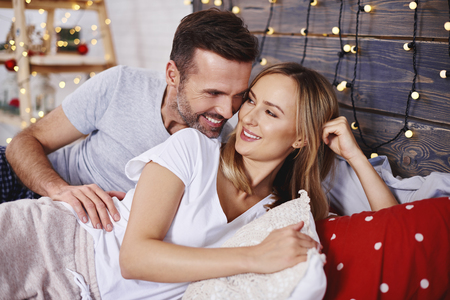 Loving couple celebrating Christmas in bed 스톡 콘텐츠