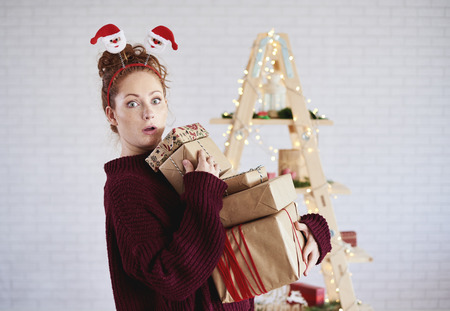 Shocked girl holding stack of christmas present