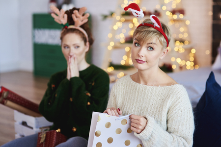 Portrait of displeased girl opening christmas present Stock Photo