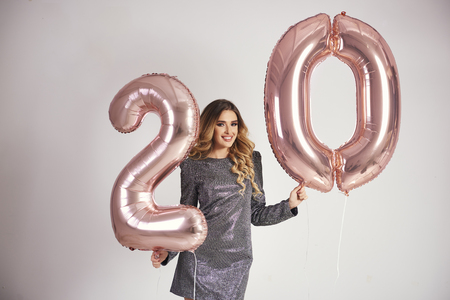 Happy young woman with golden balloons celebrating her birthday