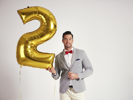 Young man with golden balloon celebrating second birthday his company Stock fotó