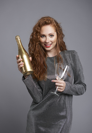 Happy woman holding a bottle of champagne and champagne flute
