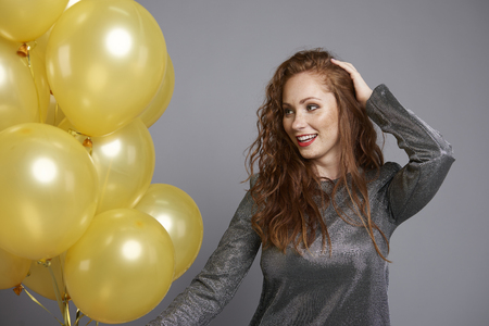 Happy woman holding bunch of balloons Stock Photo
