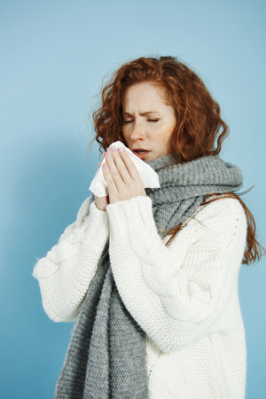 Sick girl sneezing and wiping her nose Stock Photo