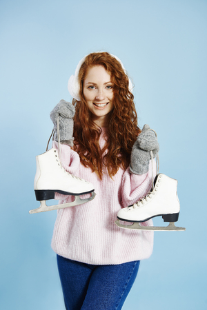Portrait of happy girl holding ice skates Banco de Imagens