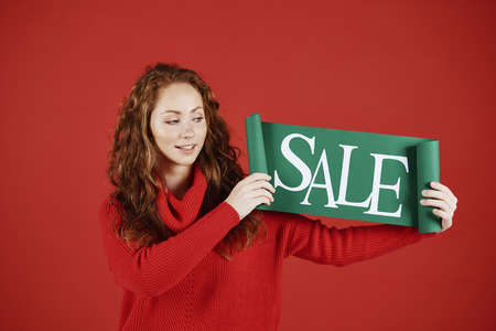 Young woman showing banner of sale at studio shot