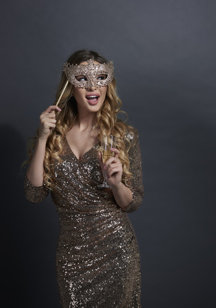 Donna urlante con maschera che beve champagne