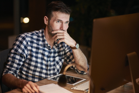 Focused businessman using a computer at night 스톡 콘텐츠