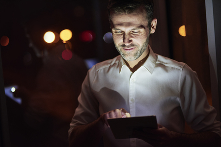 Mature men using a tablet at night 스톡 콘텐츠