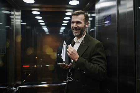 Portrait of smiling businessman listening to music in elevator