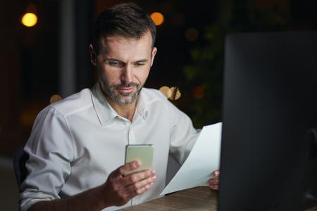 Mature businessman using mobile phone at night Imagens
