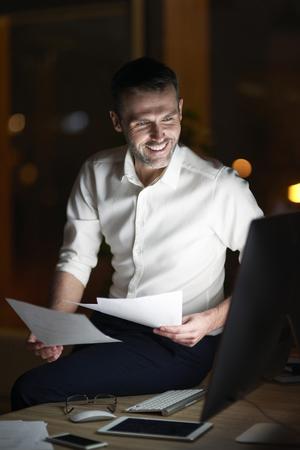 Man analyzing document at night