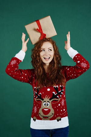 Playful girl with christmas present looking at copy space