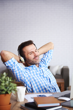 Happy man relaxing and listening to music in his office Фото со стока