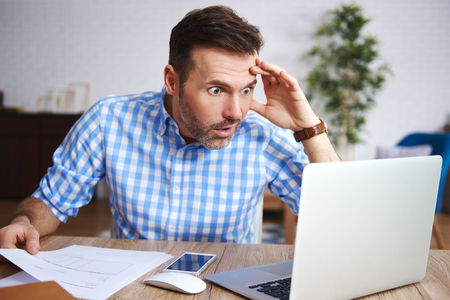 Shocked and worried man working in his office Stock Photo
