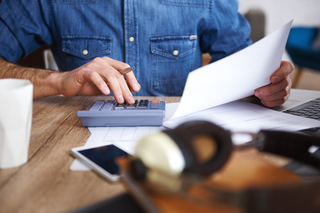 Man working with documents and calculator