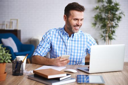 Smiling man working with laptop