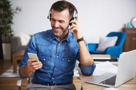 Happy man listening to music and using mobile phone Stock Photo