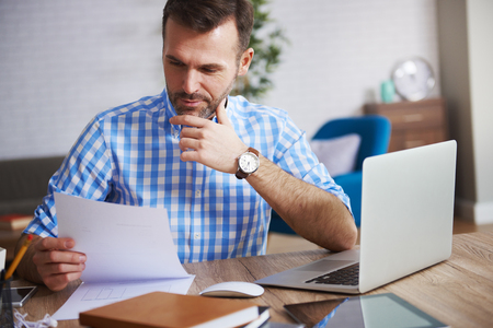 Business person reading important documents at his desk
