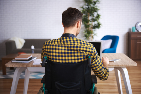 Rear view of disabled man using laptop