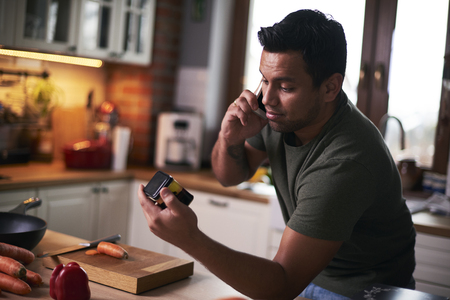 Man talking by mobile phone while cooking