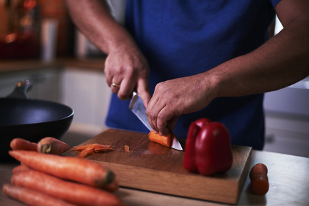 Mans hand cutting vegetable in the kitchen