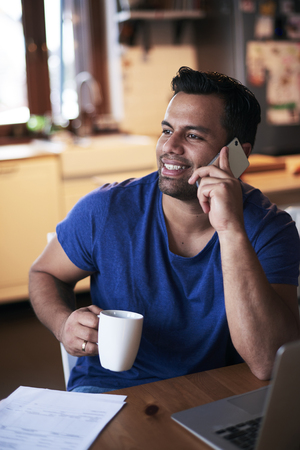 Smiling man talking by mobile phone and drinking coffee Stock Photo