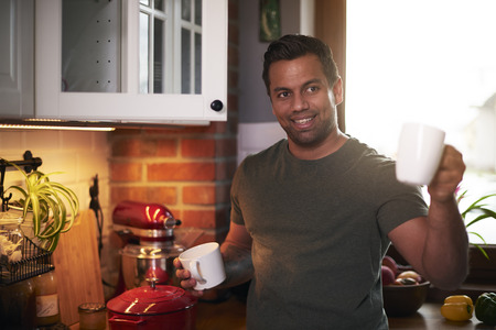 Smiling man making coffee in the kitchen