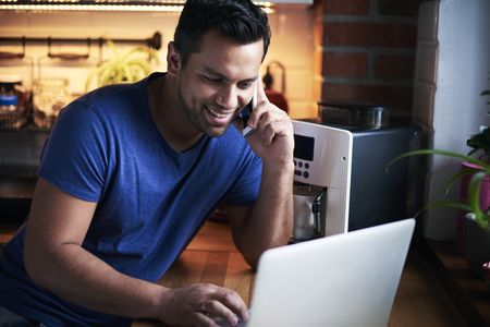 Happy man talking by mobile phone and using laptop