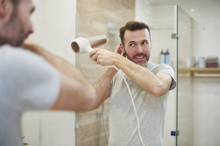 Smiling man using hairdryer in bathroom Stock Photo
