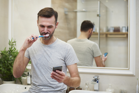 Man brushing his teeth and using mobile phone in bathroom Stock Photo