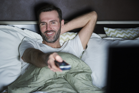 Man lying on the bed and watching tv at night