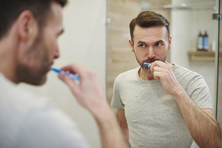 Man cleaning  teeth in bathroom Stock Photo