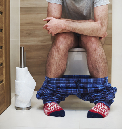 Low section of man defecating in the toilet