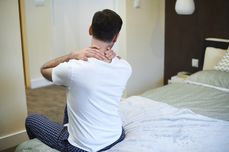 Rear view of man suffering from neckache