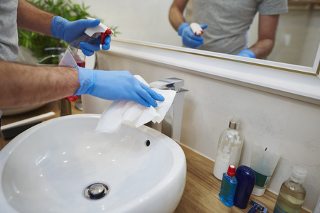 Mans hands cleaning sink in the bathroom