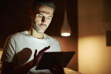 Focused man using tablet at night Stock Photo
