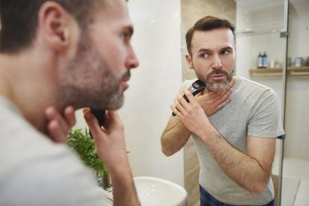 Man with electric razor shaving