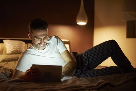 Man using a tablet in bed 스톡 콘텐츠