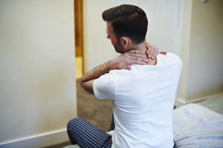Rear view of man suffering from neck pain Stock Photo