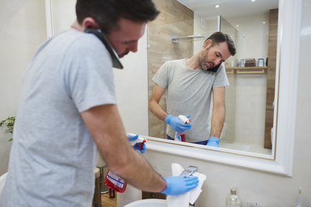 Man cleaning his bathroom and talking by mobile phone Stock Photo