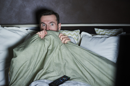 Scared man watching horror movies at night Stock Photo