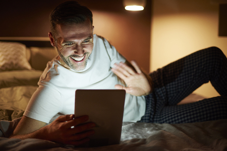 Happy man during video conference at night Stock Photo