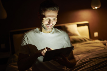 Smiling man using a  tablet at night Stock Photo
