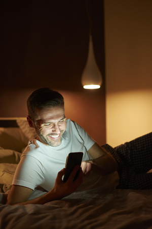 Smiling man using a mobile phone in bed Stock Photo