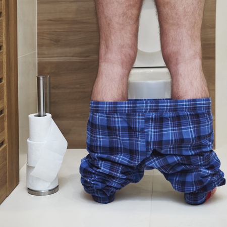 Low section of man urinating in the toilet